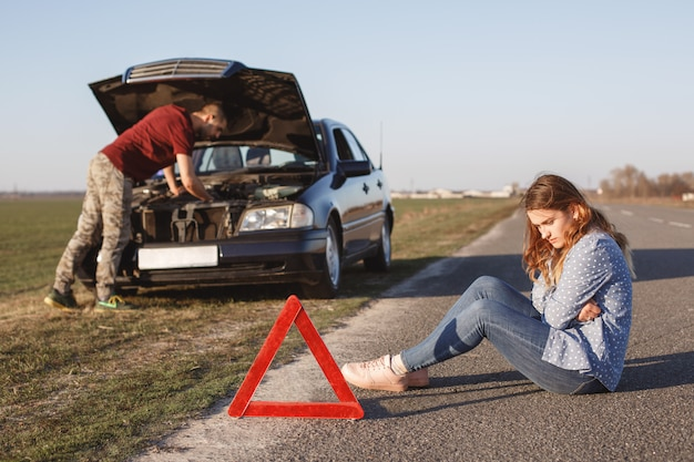 Busy young male driver tries to solve problem with damage engine of car, stands in front of opened hood while his girlfriend sit on road