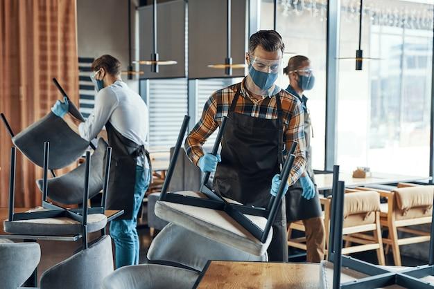 Занятые молодые мужчины-официанты в защитной спецодежде расставляют мебель в ресторане