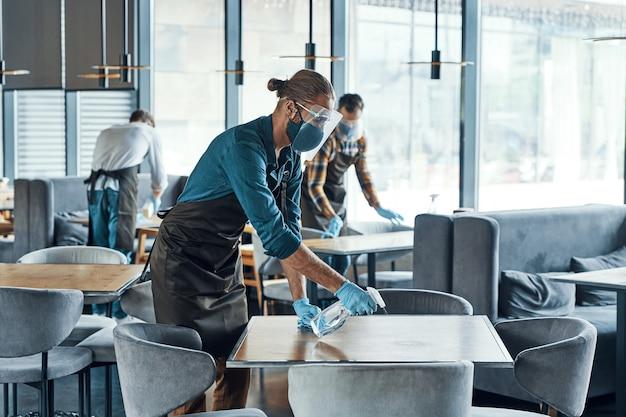 Занятые молодые мужчины-официанты в защитной спецодежде чистят столы в ресторане