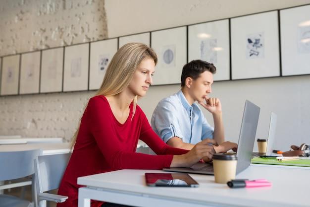 忙しい若い男性と女性のオープンスペースの共同作業事務室でラップトップに取り組んで