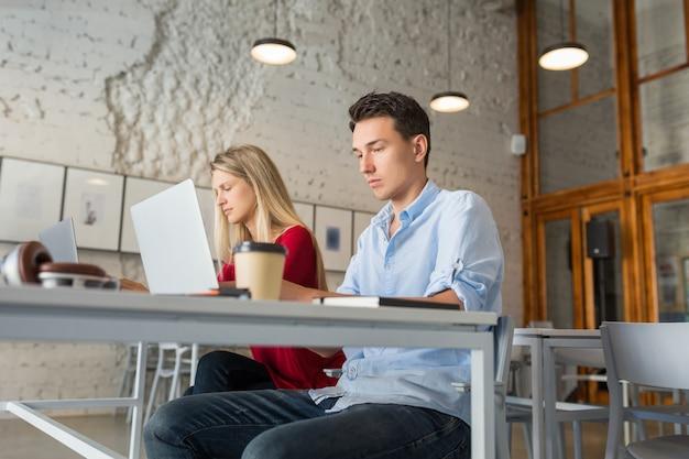 Занятый молодой мужчина и женщина, работающие на ноутбуке в офисе совместной работы на открытом воздухе