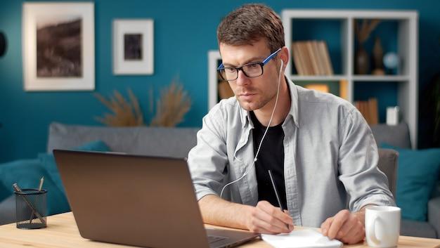 ノートパソコンの画面を見たり、ビデオを見たり、情報を読んだりしてメモをとる忙しい青年