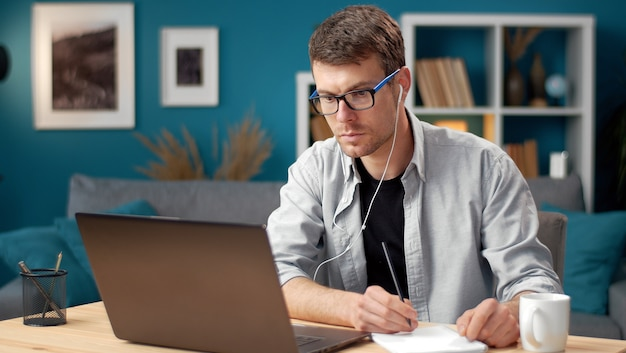 Busy young man looking at laptop screen and making notes watching video or reading information