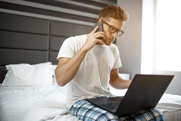 바쁜 젊은 남자가 이른 아침 침대에 앉아. 남자가 전화 통화. 그는 노트북을보고 키보드를 사용합니다. 진지하고 집중적입니다. 사업. 일광.