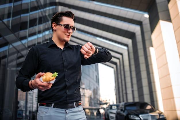 바쁜 젊은이 서 선글라스를 통해 시계를 봐. 그는 짠 크로 이산을 손에 든다. 남자가 조금 웃어요.