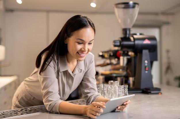タッチパッドがテーブルに寄りかかってネットサーフィンをしている忙しい若いマネージャーが、レストランで準備するための好奇心旺盛なレシピやコースを探しています