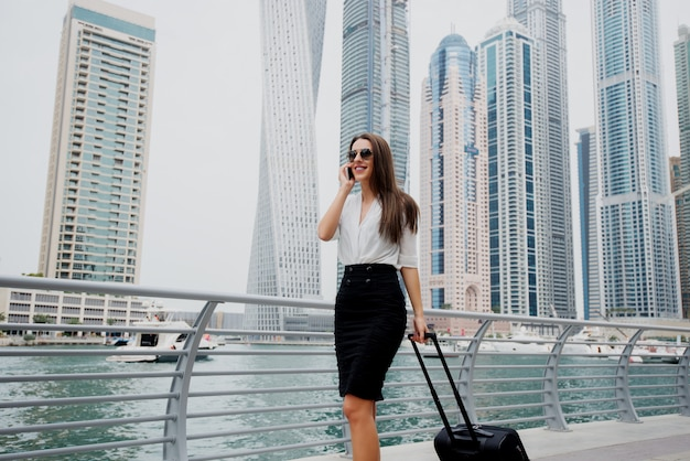 Busy young modern business woman in suit pulling a suitcase in a dubai marine. walking to her office and talking on a telephone..