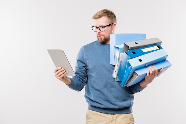 Busy young office manager with digital tablet and stack of folders in hands surfing in the net in front of camera