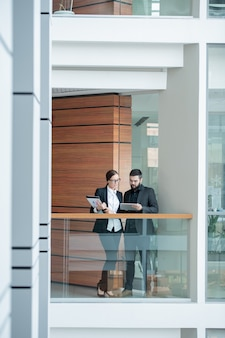 Busy young office workers in formalwear standing on balcony in office center and using tablet while discussing business plan
