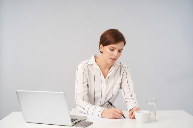Деловая молодая довольно коротко стриженная брюнетка с повседневной прической держит ручку в руке, делая заметки перед важной встречей, в белой полосатой рубашке на белом