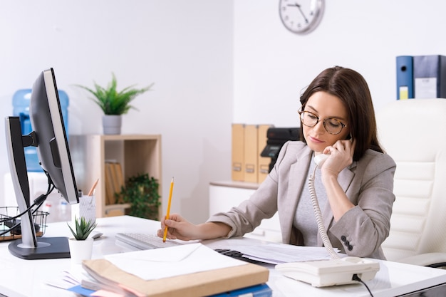 Занятый молодой секретарь или офис-менеджер в строгой одежде и в очках разговаривает по телефону и просматривает бумаги за столом