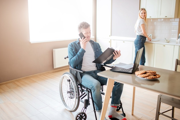 Busy young student on wheelchair studying and taking on phone. guy with special needs and disability. holding opened folder. young woman stand at stove and cooking