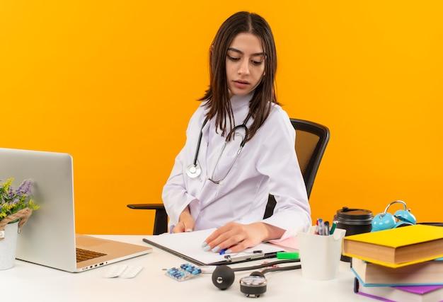 オレンジ色の壁の上のラップトップとドキュメントとテーブルに座って聴診器と白衣で忙しい若い女性医師