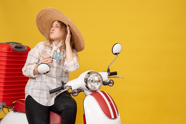모자를 쓰고 오토바이에 앉아 티켓을 들고 바쁜 젊은 여성이 노란색에 대한 마지막 가십을 듣고