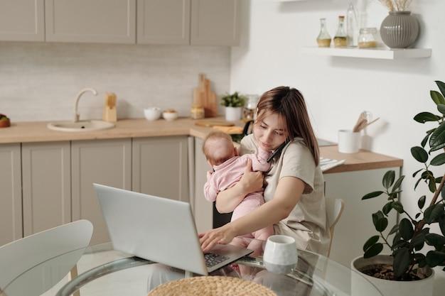 노트북을 사용하고 스마트폰으로 말하는 아기와 함께 바쁜 젊은 여성