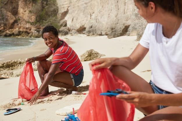 忙しい若い女性は、プラスチック廃棄物で完全に汚染されたビーチをきれいにします