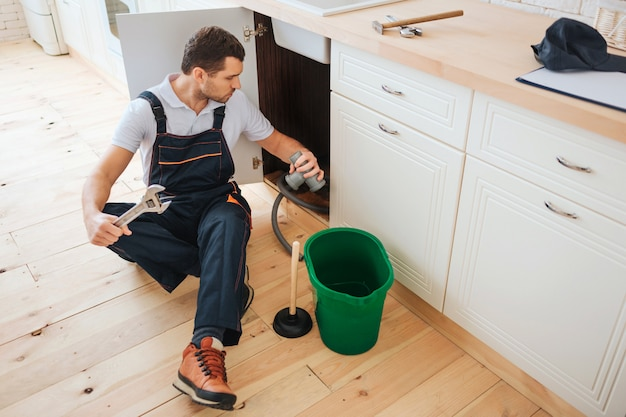 Busy young worker sits on floor in kitchen
