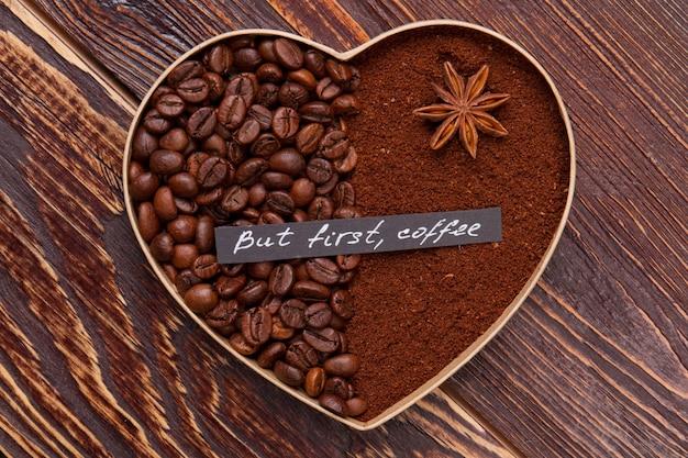 Но сначала кофе. декоративное кофейное сердце из кофейных зерен и порошка растворимого кофе на деревянной поверхности.