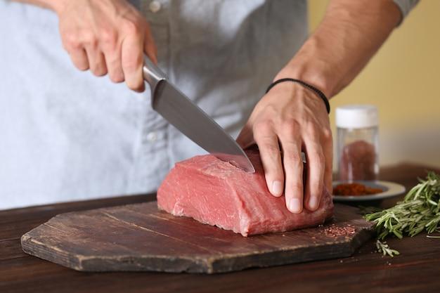 Мясник режет свинину на кухне