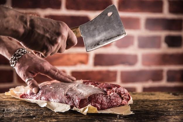 肉屋の男が肉屋で生のビーフステーキを手で切る。