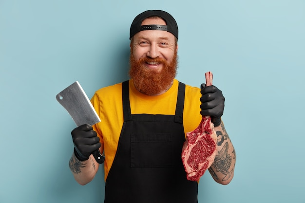 Butcher man with ginger beard holding meat