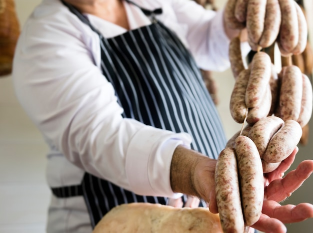 Мясник продает колбасы на веревке