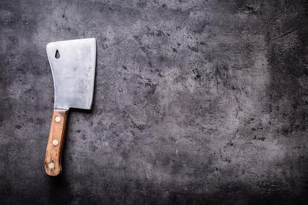 푸줏간. 어두운 콘크리트나 나무 주방 판자에 천 타월을 얹은 빈티지 정육점 고기 절단기.