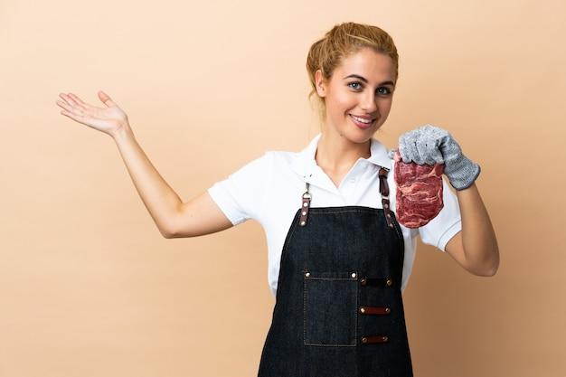 Женщина-мясник в фартуке, подающая свежее нарезанное мясо над изолированной стеной, протягивает руки в сторону, приглашая прийти