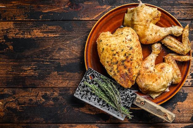 木製のテーブルの上に肉付きの焼きチキン。暗い背景。上面図。スペースをコピーします。