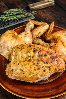 木製のテーブルの上に肉付きの焼きチキン。暗い背景。上面図。