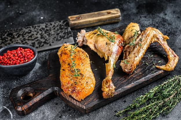 Butchered baked duck, breast fillet, wing, leg. black background. top view.