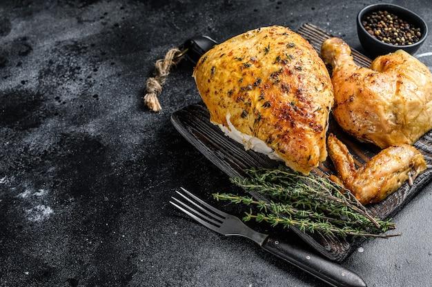 鶏肉の丸焼き焼き。黒の背景。上面図。スペースをコピーします。