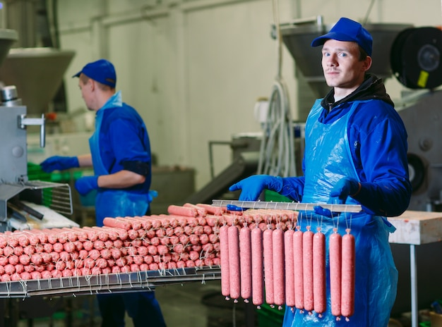 Butchers processing sausages at meat factory.
