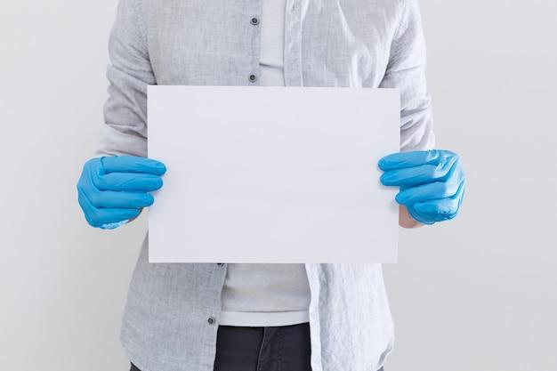 空白のメモを持っている執事またはコンシェルジュの手。白で隔離された右側から手を伸ばした水平フォーマットの腕。