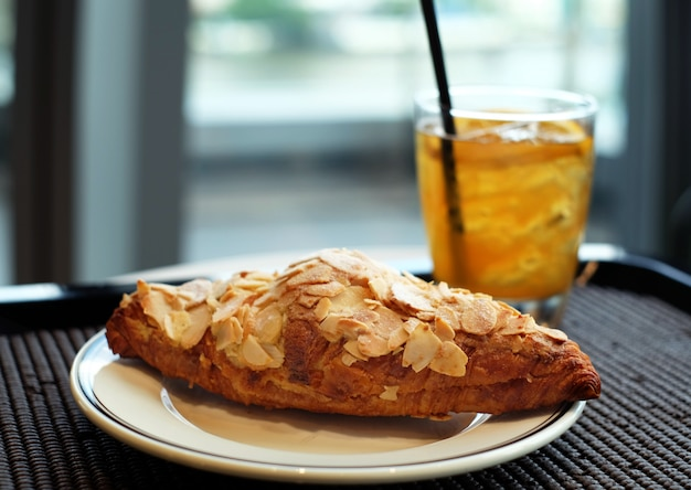Butter almond croissant with iced tea background