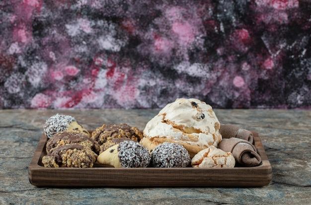 Сливочное и шоколадное печенье в деревянной тарелке.