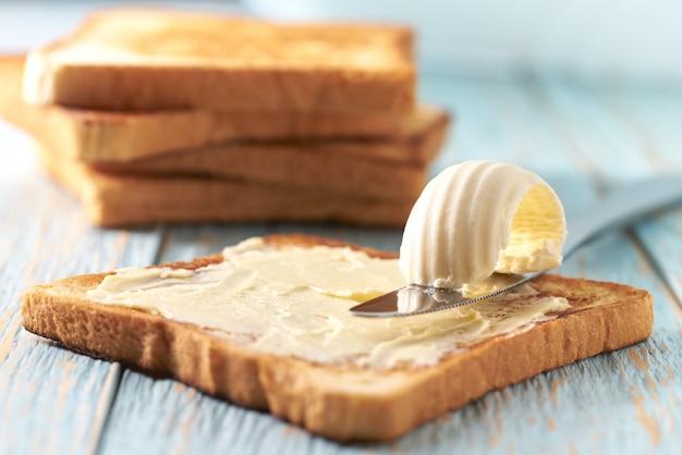 青い木製のテーブルにバターとトーストしたパンのスライス。
