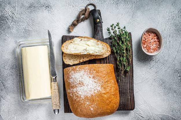 버터 블록 및 허브와 함께 나무 보드에 빵의 슬라이스 토스트. 화이트 테이블. 평면도.