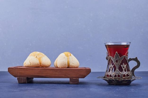 お茶のグラスと木製の大皿にバタークッキー。高品質の写真