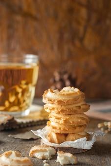 나무 테이블 배경에 쌓인 버터 쿠키와 차 한 잔, 세로 사진.