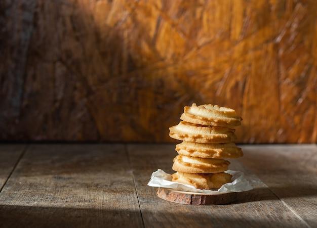 나무 테이블 배경에 쌓인 버터 쿠키.