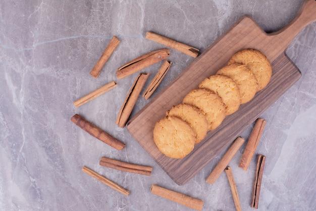 Сливочное печенье с палочками корицы на деревянном блюде.