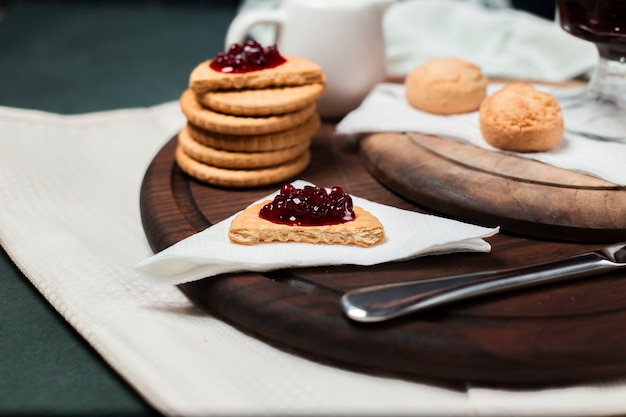 Butter cookies with strawberry jam on a wooden board on a piece of tissue