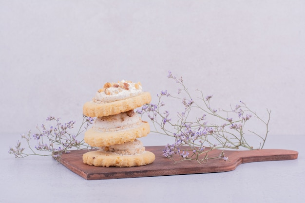 Biscotti al burro con panna montata su piatto di legno.