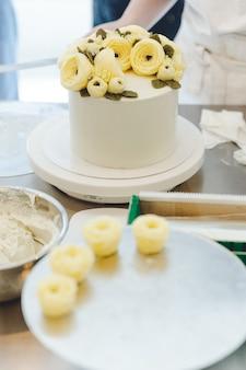 백그라운드에서 화이트 케이크와 케이크를 꾸미기를위한 쟁반에 버터 크림 꽃.