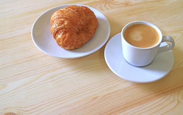 Круассан с маслом и чашка горячего кофе на деревянном столе