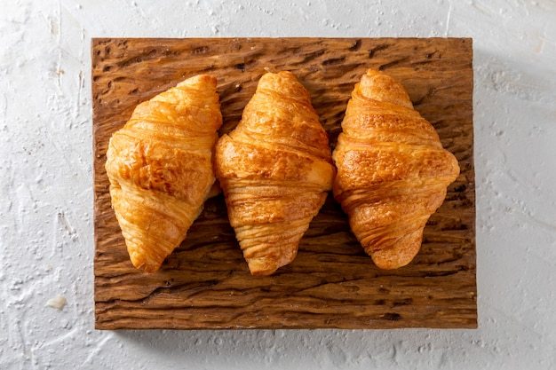 Butter croissants on a rustic wooden board.
