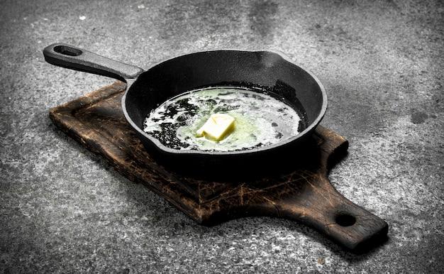 古い鍋にバターを塗る。素朴な背景に。