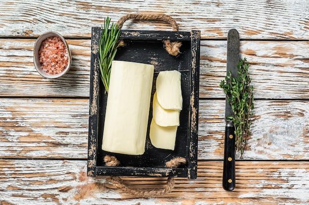 허브와 함께 나무 쟁반에 버터 마가린 블록. 흰색 나무 테이블. 평면도.