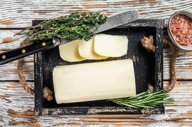 Блок сливочного маргарина в деревянном подносе с зеленью
